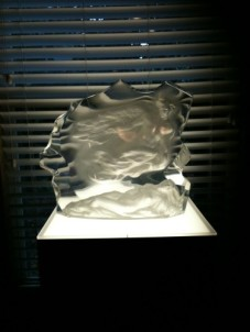 Etched glass sculpture on ambient lighted pedestal