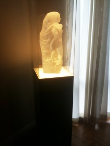 Frosted sculpture on ambient lighted pedestal with clear acrylic dust cover