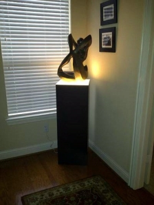 Large sculpture on ambient lighted pedestal w/ backlighting